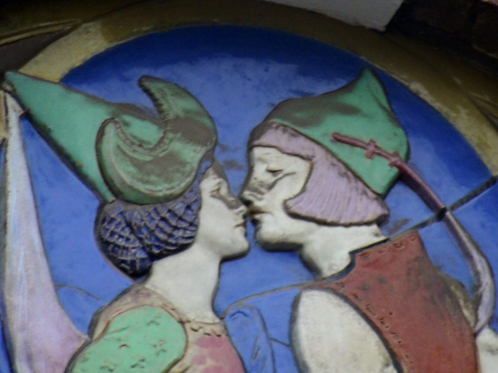 Ceramic detail of a young man and woman about to kiss.