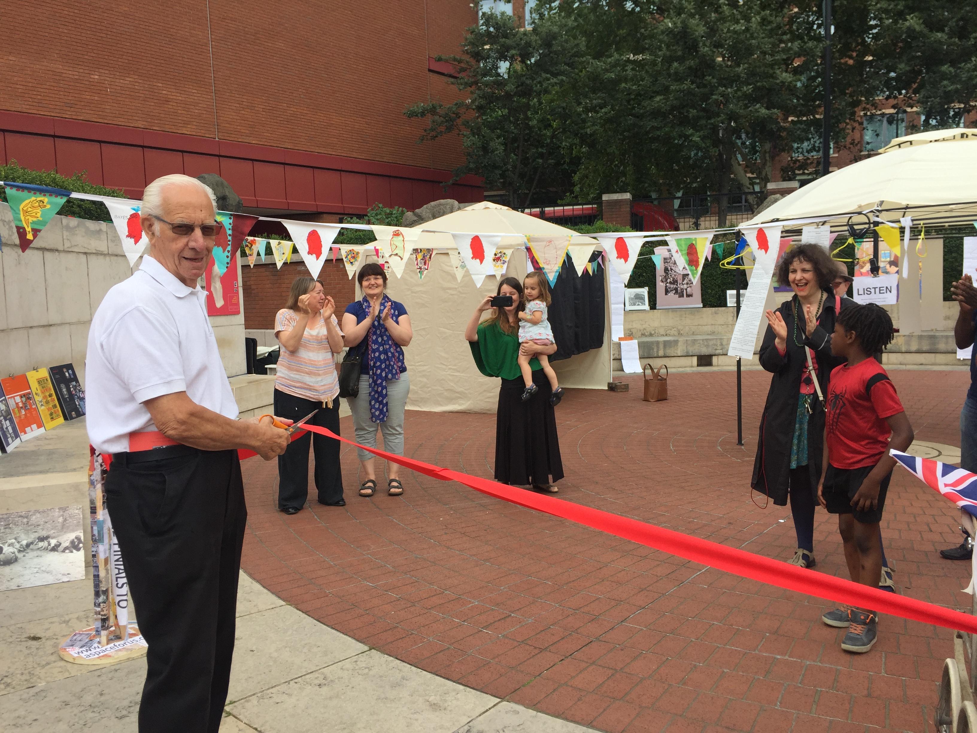 A man cutting a red tape in public.
