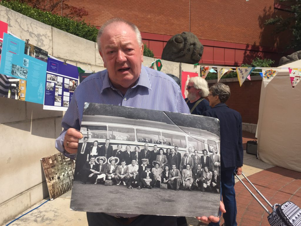 A man standing holding an old photograph.