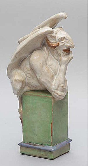 A ceramic devil with head in his hands.