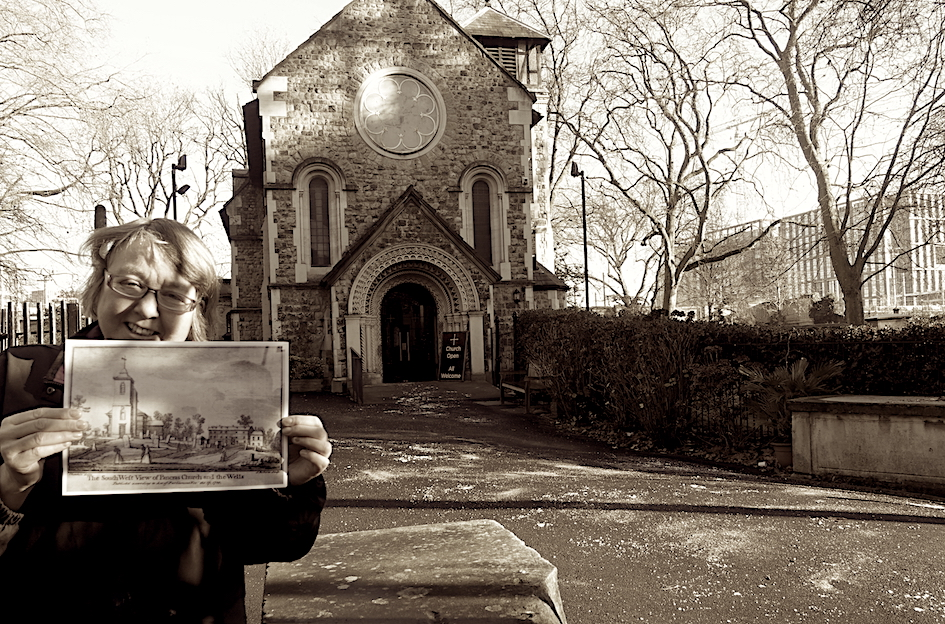 A woman holding a photo outside a church.