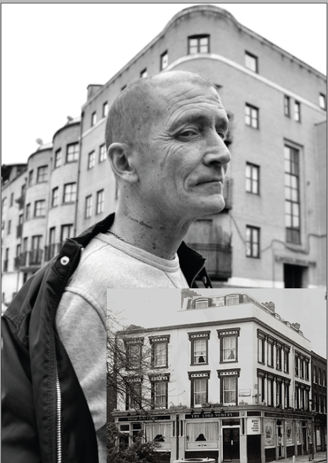 Man standing outside street with old photo of pub.