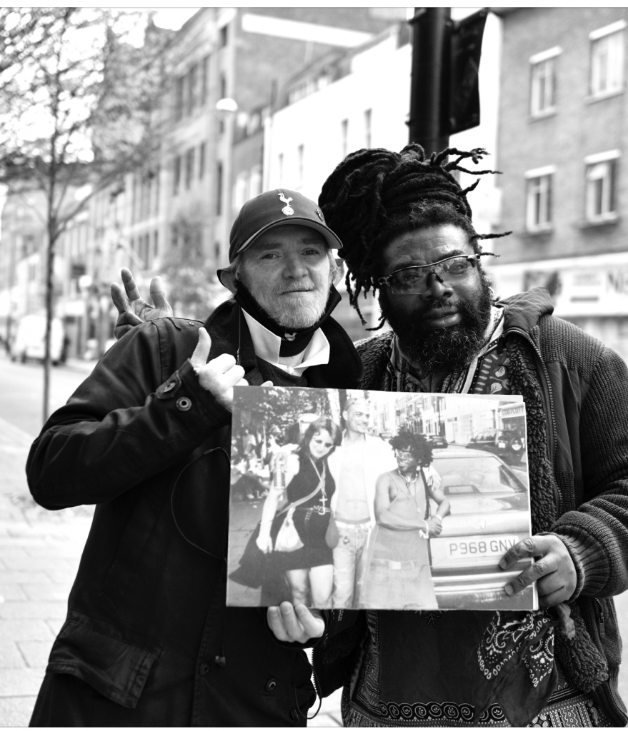 Two men holding an old photo of festival .