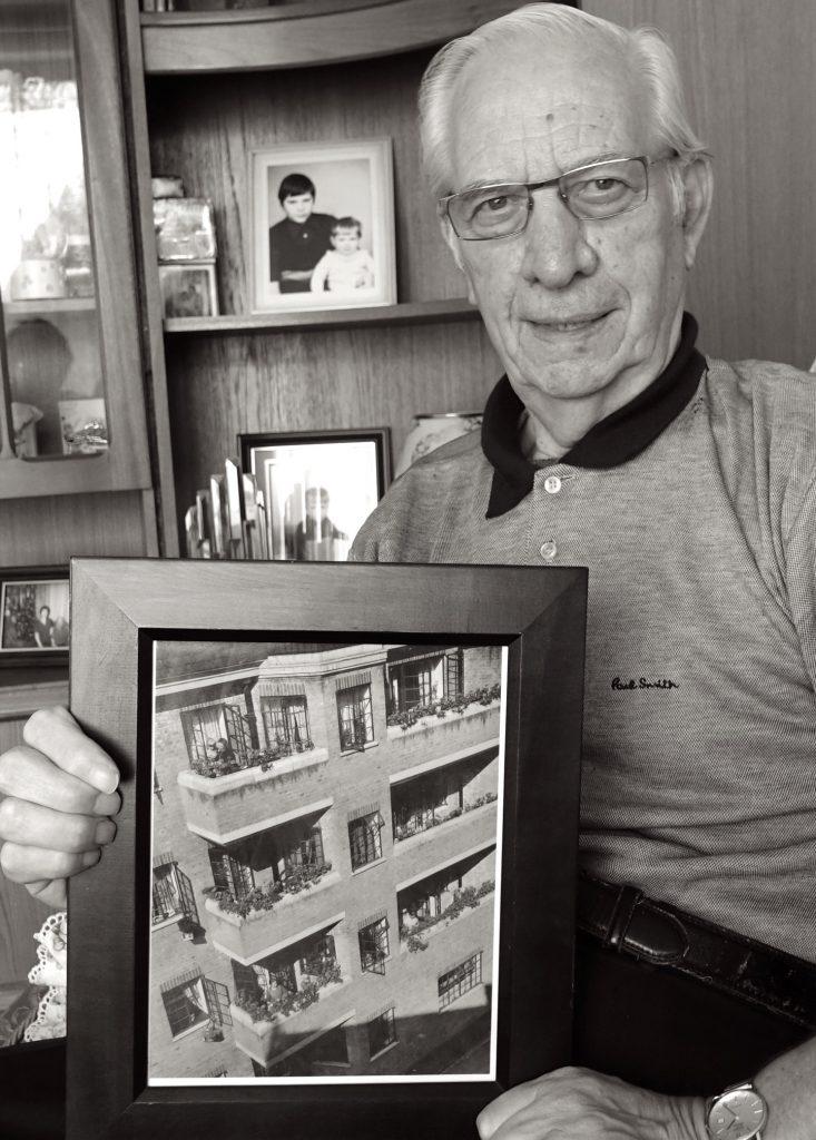 Older man holding photo.