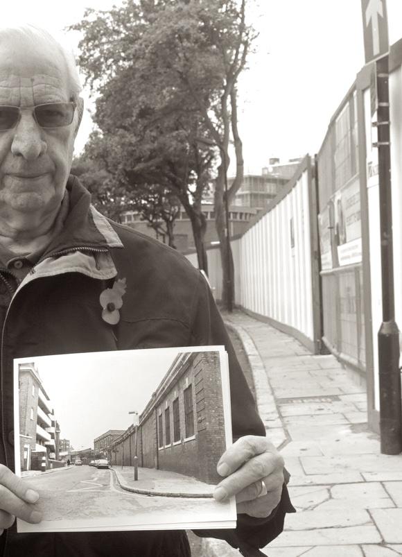 Old man at demolition site of old building.