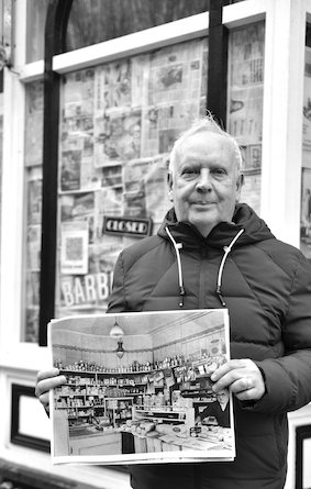 Middle age man in street holding old photo of shop