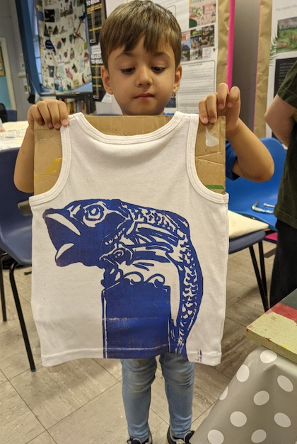 Boy holding a T-shirt with a fish on it.